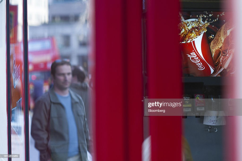 Coca-Cola Co. signage is displayed on drink dispenser at a restaurant as a pedestrian passes by outside in San Francisco, California, U.S., on Wednesday, Feb. 6, 2013. The Coca-Cola Co. is scheduled to release earnings data on Feb. 12. Photographer: David Paul Morris/Bloomberg via Getty Images