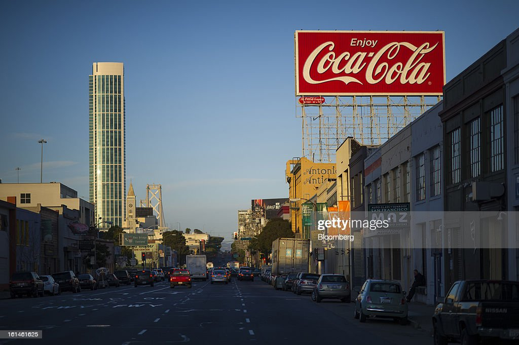 Coca-Cola Co signage is displayed on top of a building as cars drive past on Bryant Street in San Francisco, California, U.S., on Wednesday, Feb. 6, 2013. The Coca-Cola Co. is scheduled to release earnings data on Feb. 12. Photographer: David Paul Morris/Bloomberg via Getty Images