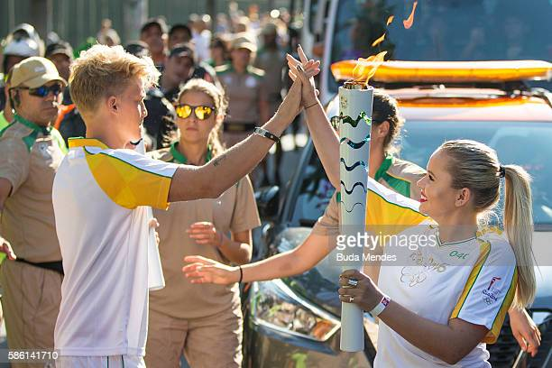 CocaCola Olympic Torch Bearer Cody Simpson shares a #ThatsGold moment with his little sister Alli as he hands the Olympic Flame over to her prior to...