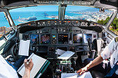 Airplane cockpit flying on port of Malaga from the Gibralfaro Castle, Andalusia, Spain, with pilots arms and blank white papers for copy space.
