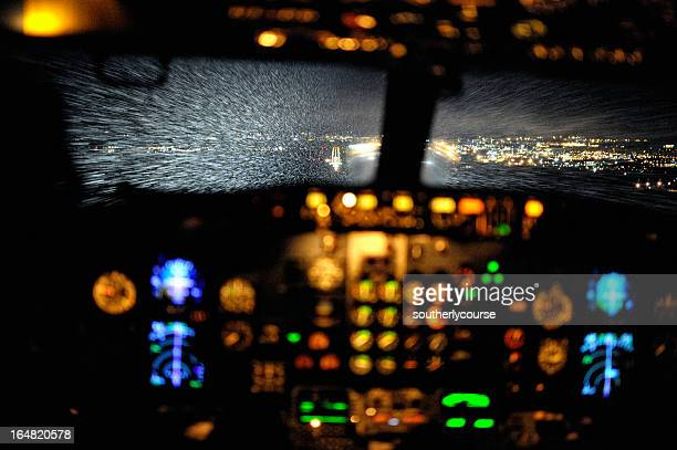 Cockpit View of Aircraft Approching Airport During Snowfall at Night