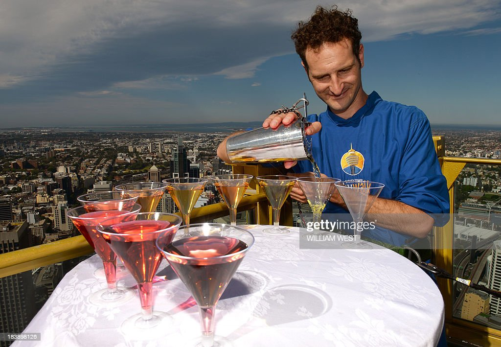 Cocktail maker Jeremy Thomas pours martinis against the Sydney city skyline, 268 metres above street level on the Sydney Eye Tower on October 10, 2013. Cocktail Club will be holding Sydneys highest cocktail classes on the Observation Deck during October as part of the month-long Sydney Good Food Festival. AFP PHOTO/William WEST