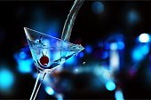 Pouring martini cocktail on dark background