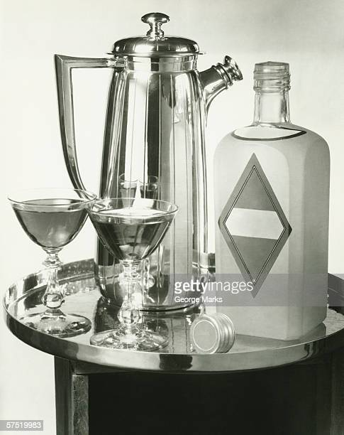 Cocktail shaker, two glasses and bottle with gin bottle standing on tray, (B&W), close-up