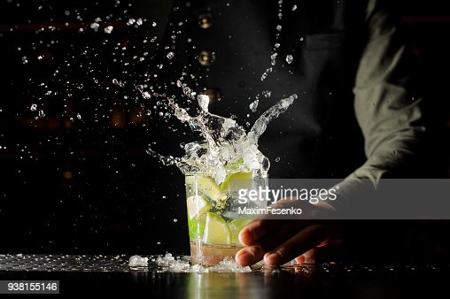 Cocktail splash with ice cubes and lime : Stock Photo