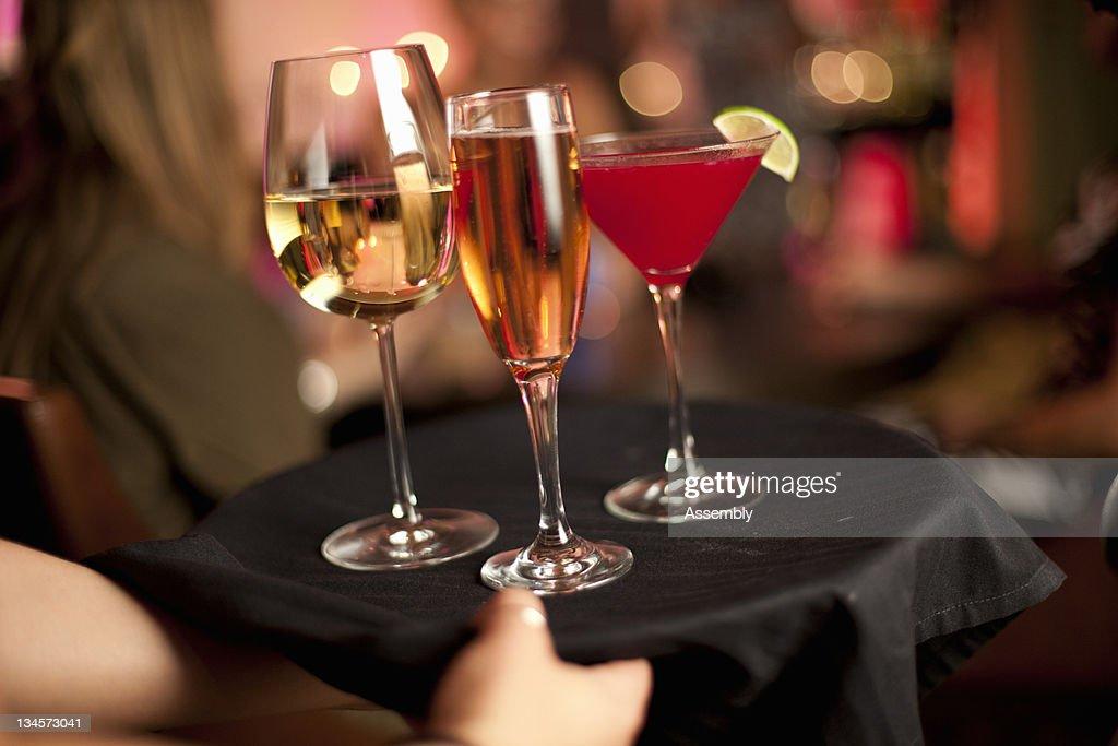 A cocktail waitress serves drinks. : Stock Photo