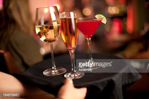 A cocktail waitress serves drinks. : Stock Photo