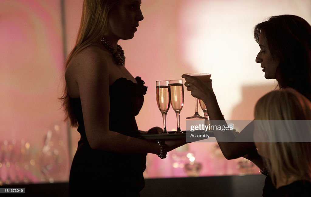 Cocktail waitress serves drinks to women. : Stock Photo