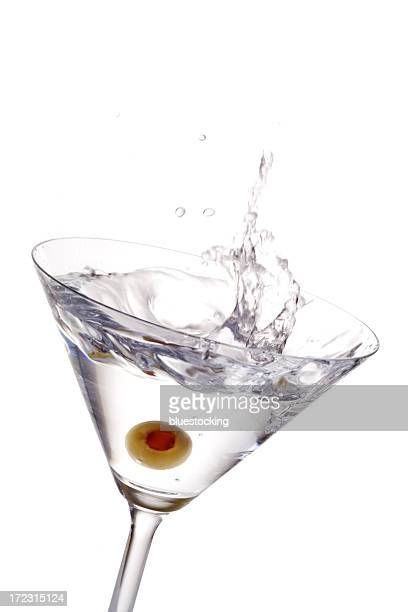 A cocktail with olive splashing