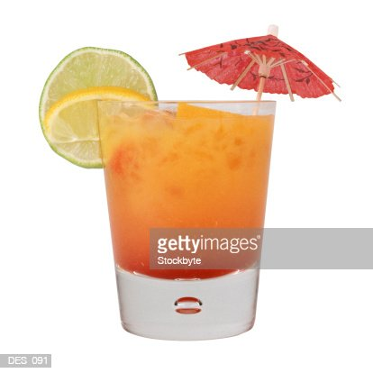 Cocktail with paper umbrella and fruit garnish, side view : Stock Photo