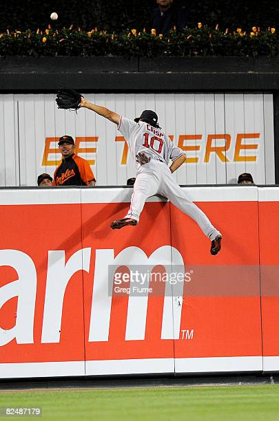 Coco Crisp of the Boston Red Sox flips over the outfield wall trying to catch a home run by Ramon Hernandez of the Baltimore Orioles August 20 2008...