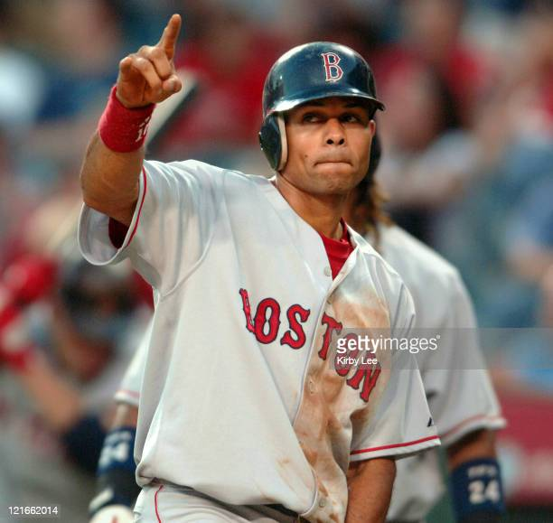 Coco Crisp of the Boston Red Sox points skyward in celebration after scoring on a tworun home run by David Ortiz in the first inning of 54 victory...