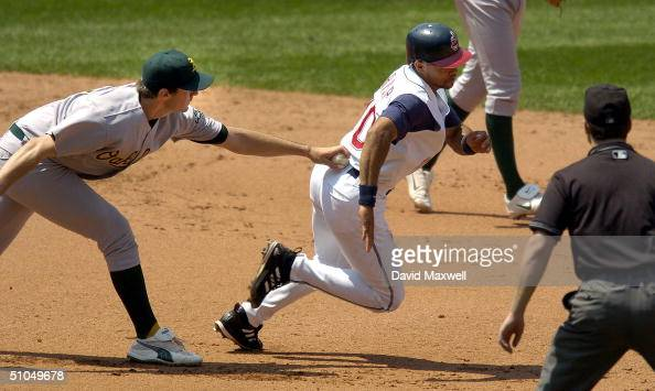Coco Crisp of the Cleveland Indians is tagged out after being caught in a rundown by pitcher Barry Zito of the Oakland Athletics in the sixth inning...
