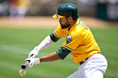 Coco Crisp of the Oakland Athletics attempt to bunt against the Baltimore Orioles during the first inning at Oco Coliseum on July 20 2014 in Oakland...