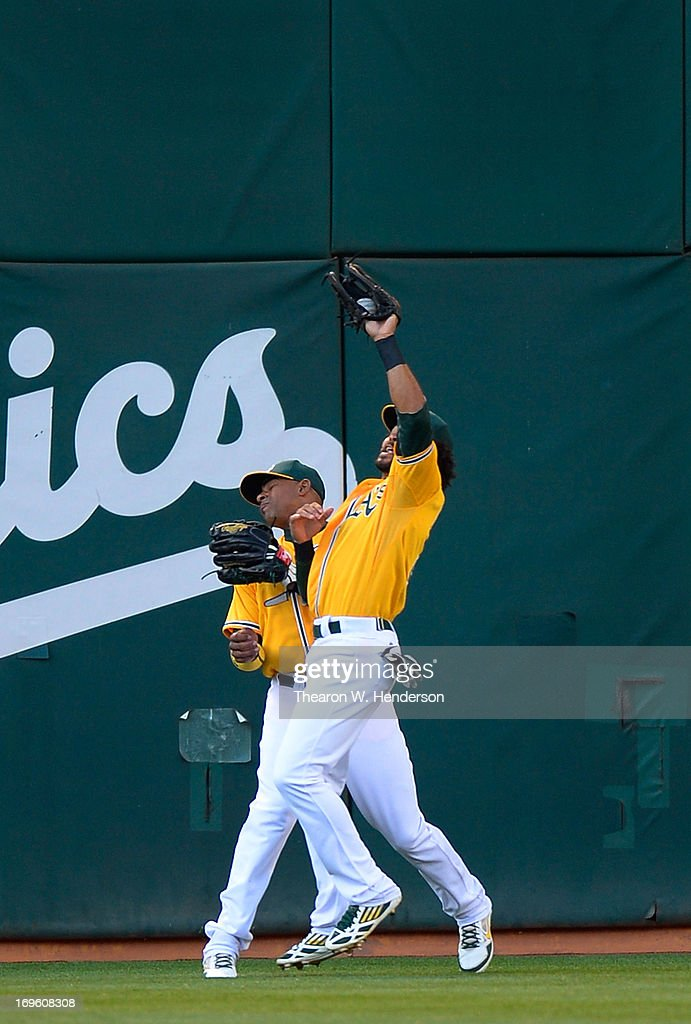 Coco Crisp #4 of the Oakland Athletics catches a fly ball off the bat of Buster Posey #8 of the San Francisco Giants, and avoids colliding with Yoenis Cespedes #52 in the first inning at O.co Coliseum on May 28, 2013 in Oakland, California.