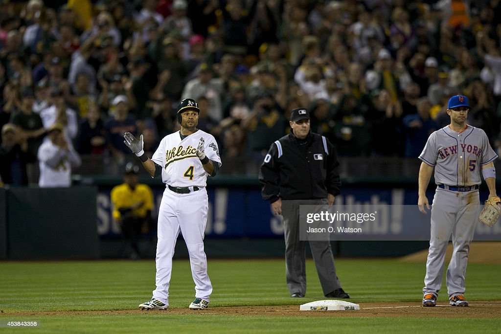 Coco Crisp #4 of the Oakland Athletics celebrates at third base after hitting a three run triple in front of David Wright #5 of the New York Mets and umpire Marty Foster #60 during the fourth inning of an interleague game at O.co Coliseum on August 19, 2014 in Oakland, California.