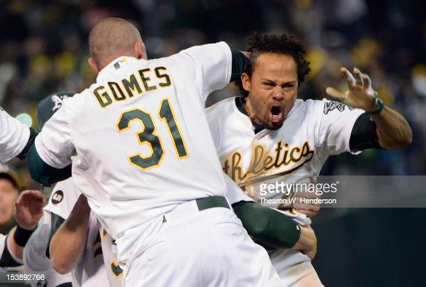 Coco Crisp of the Oakland Athletics celebrates with the team after hitting a walkoff single against the Detroit Tigers during Game Four of the...