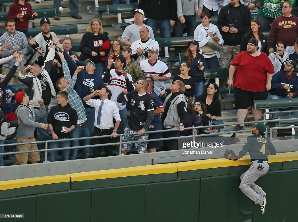 <a gi-track='captionPersonalityLinkClicked' href=/galleries/search?phrase=Coco+Crisp&family=editorial&specificpeople=206376 ng-click='$event.stopPropagation()'>Coco Crisp</a> #4 of the Oakland Athletics climbs the wall and watches as fans try to catch a home run ball hit by Tyler Flowers of the Chicago White Sox at U.S. Cellular Field on June 7, 2013 in Chicago, Illinois.