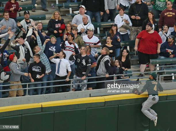 Coco Crisp of the Oakland Athletics climbs the wall and watches as fans try to catch a home run ball hit by Tyler Flowers of the Chicago White Sox at...