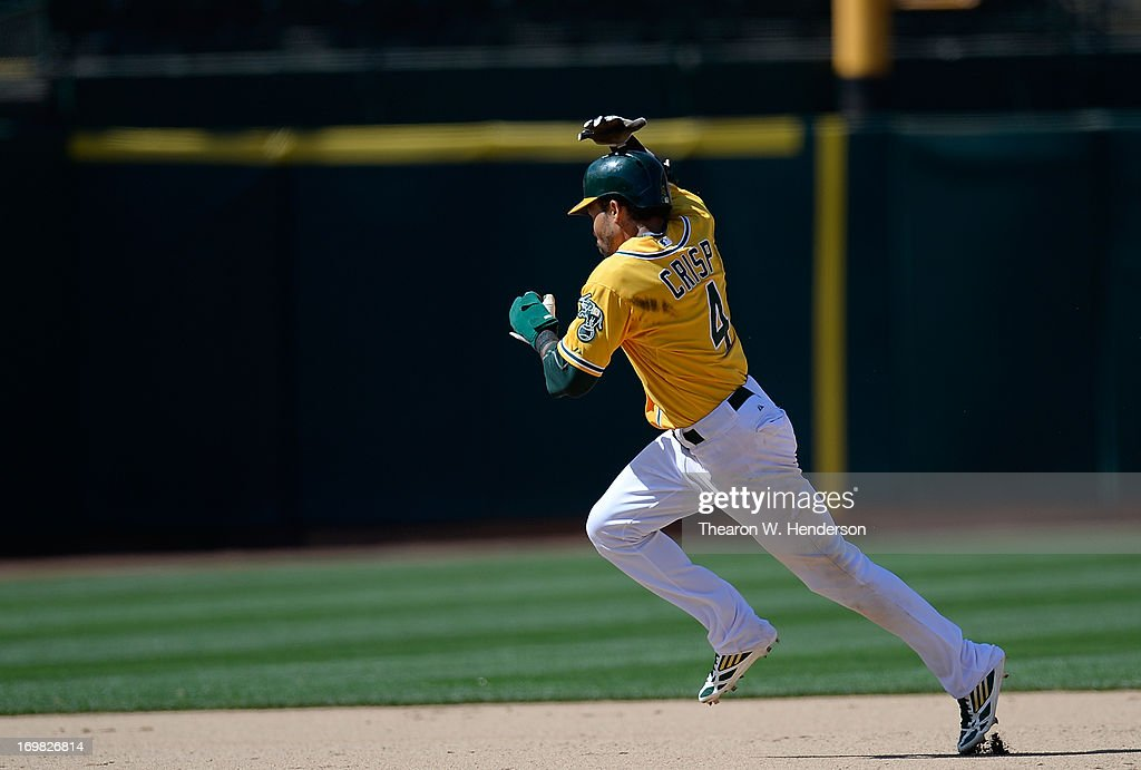 Coco Crisp #4 of the Oakland Athletics holds on to his helmet as he rounds the bases to score his second run of the game against the Chicago White Sox during the eighth inning at O.co Coliseum on June 2, 2013 in Oakland, California. The Athletics defeated the White Sox 2-0.