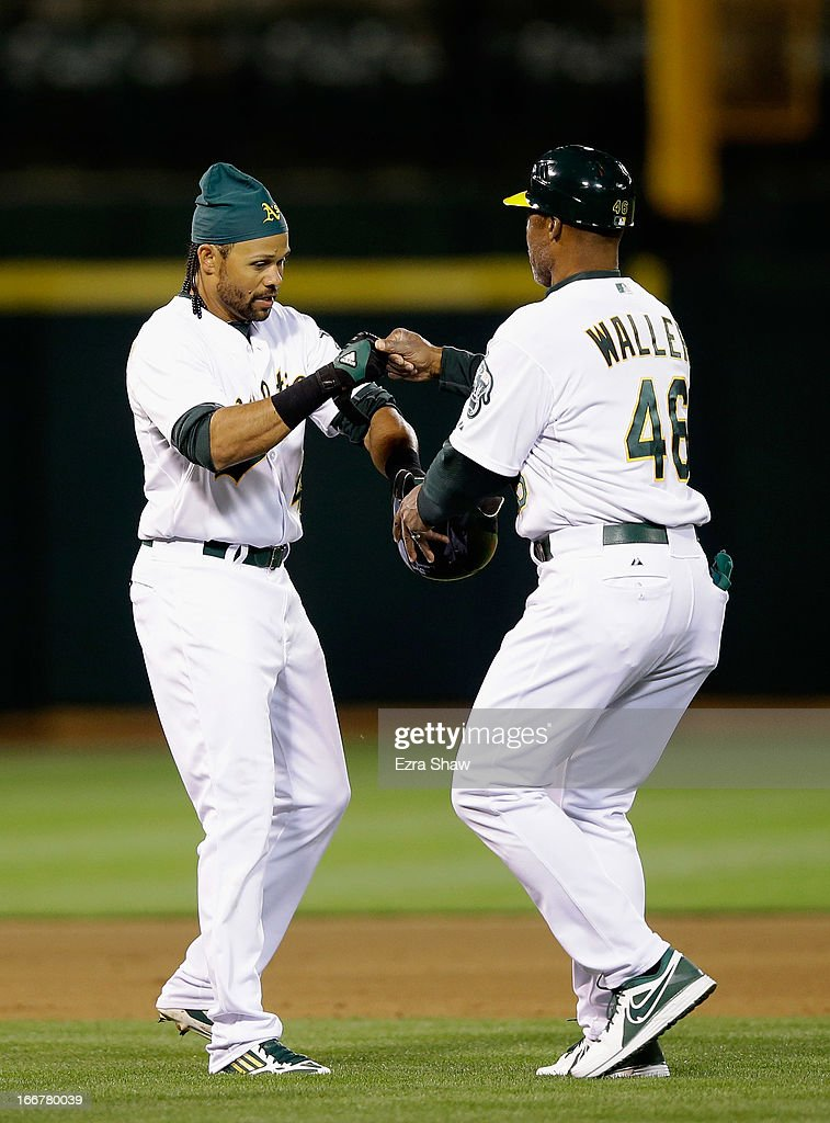 Coco Crisp #4 of the Oakland Athletics is congratulated by first base coach Tye Waller #46 when Waller returns Crisp's helmet after Crisp hit a triple that scored Eric Sogard #28 in the fifth inning of their game against the Houston Astros at O.co Coliseum on April 16, 2013 in Oakland, California.