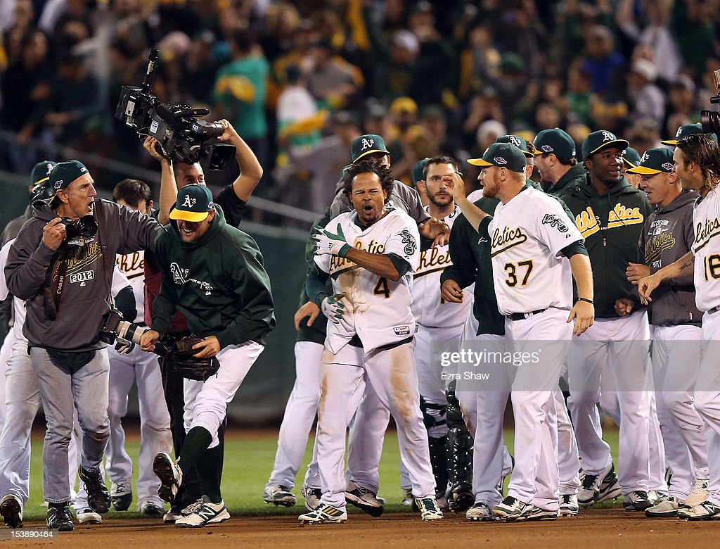<a gi-track='captionPersonalityLinkClicked' href=/galleries/search?phrase=Coco+Crisp&family=editorial&specificpeople=206376 ng-click='$event.stopPropagation()'>Coco Crisp</a> #4 of the Oakland Athletics is congratulated by teammates after he hit a game-winning single to beat the Detroit Tigers in the ninth inning of Game Four of the American League Division Series at Oakland-Alameda County Coliseum on October 9, 2012 in Oakland, California.