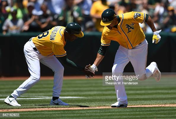 Coco Crisp of the Oakland Athletics is congratulated by third base coach Ron Washington after he hit a solo home run against the Milwaukee Brewers in...