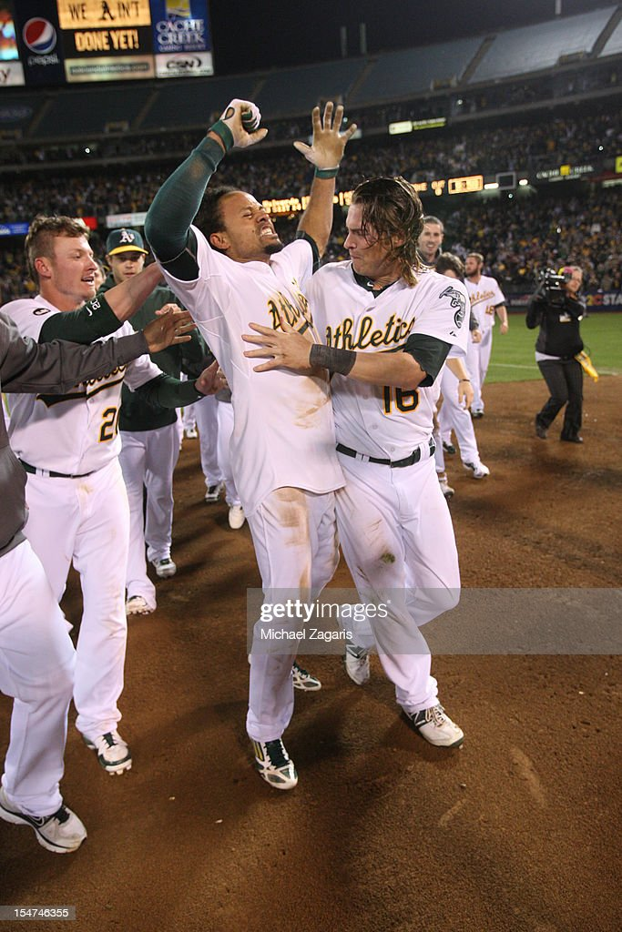 Coco Crisp #4 of the Oakland Athletics is mobbed by Josh Donaldson #20 and Josh Reddick #16 after hitting a walk-off single following the game against the Detroit Tigers at the Oakland-Alameda County Coliseum on October 10, 2012 in Oakland, California. The Athletics defeated the Tigers 4-3.