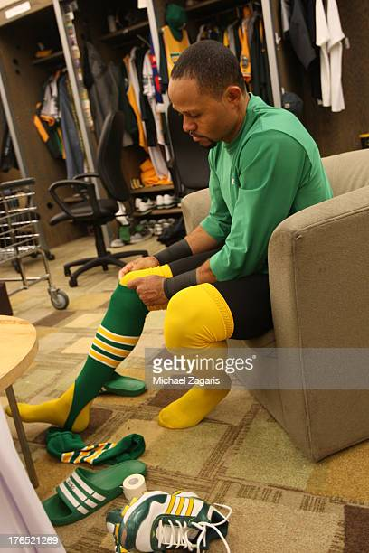 Coco Crisp of the Oakland Athletics puts on socks from the 1969 team in the clubhouse prior to the game against the Los Angeles Angels of Anaheim at...