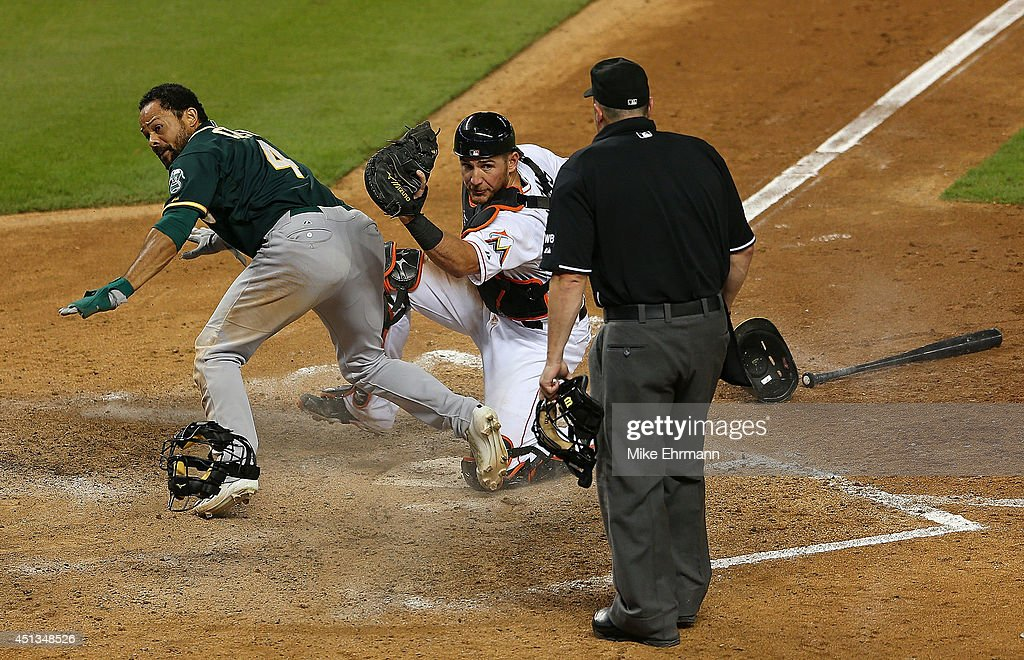 <a gi-track='captionPersonalityLinkClicked' href=/galleries/search?phrase=Coco+Crisp&family=editorial&specificpeople=206376 ng-click='$event.stopPropagation()'>Coco Crisp</a> #4 of the Oakland Athletics slides into catcher <a gi-track='captionPersonalityLinkClicked' href=/galleries/search?phrase=Jeff+Mathis&family=editorial&specificpeople=660661 ng-click='$event.stopPropagation()'>Jeff Mathis</a> #6 of the Miami Marlins during a game at Marlins Park on June 27, 2014 in Miami, Florida. Crisp was originally called out and after review the play was overturned.