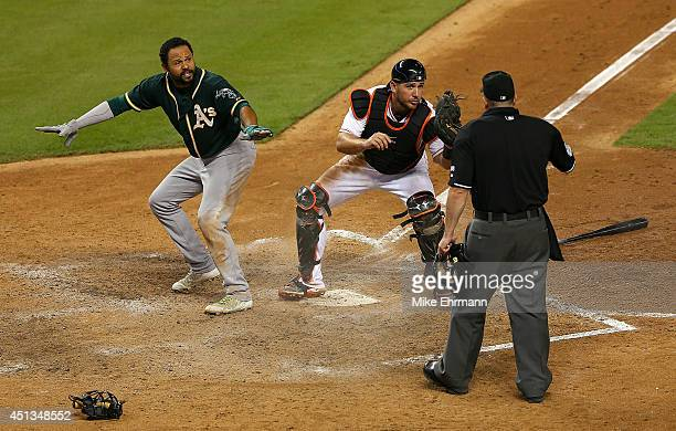 Coco Crisp of the Oakland Athletics slides into catcher Jeff Mathis of the Miami Marlins during a game at Marlins Park on June 27 2014 in Miami...