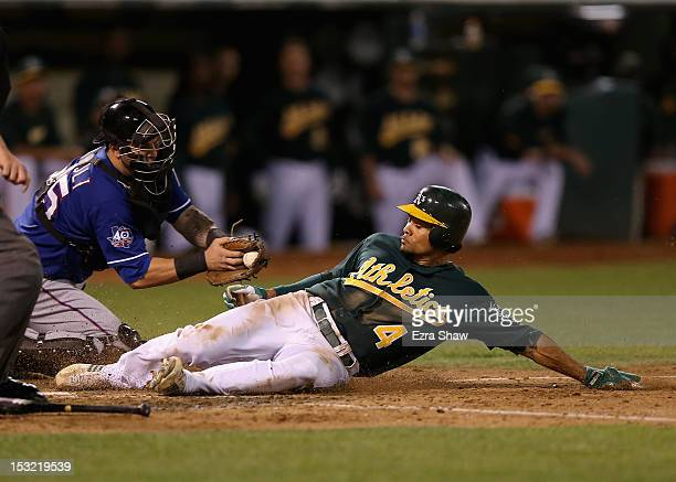 Coco Crisp of the Oakland Athletics slides safely past Mike Napoli of the Texas Rangers to score on a sacrifice fly by Brandon Moss in the fifth...