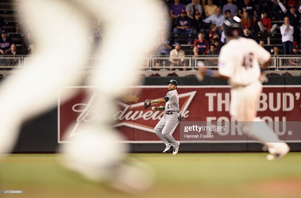 Coco Crisp #4 of the Oakland Athletics throws the ball back to the infield after an RBI single off the bat of Joe Mauer of the Minnesota Twins in the seventh inning of the game on May 6, 2015 at Target Field in Minneapolis, Minnesota. The Twins defeated Athletics 13-0.
