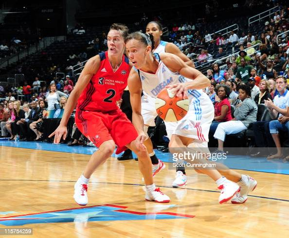 Coco Miller of the Atlanta Dream drives against her twin sister Kelly Miller of the Washington Mystics at Philips Arena on June 9 2011 in Atlanta...
