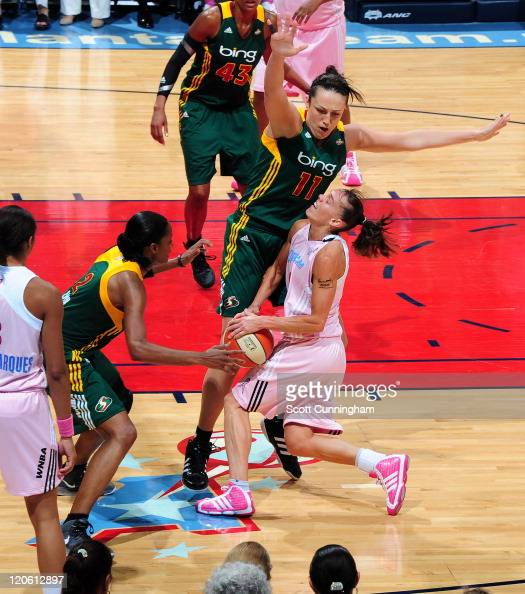 Coco Miller of the Atlanta Dream is defended by Swin Cash and Ewelina Kobryn of the Seattle Storm at Philips Arena on August 7 2011 in Atlanta...