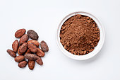Heap of Cocoa Beans and Grounded Cocoa on the White Background Closeup