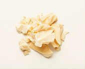 Pieces of cocoa butter isolated on white background. Heap of white chocolate, cutout