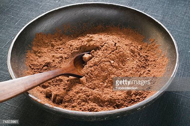 Cocoa powder in bowl with wooden spoon