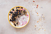 Coconut blueberry breakfast bowl with chia and sesame seeds on concrete. Top view, blank space