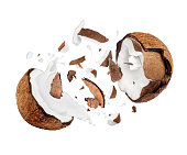 Coconut broken in the air into two halves with milk splashes