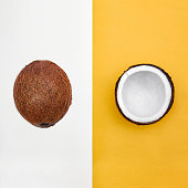 Whole coconut in peel and half of coconut are lying on two-tone background Top view Trendy colorful photo mockup with space for text