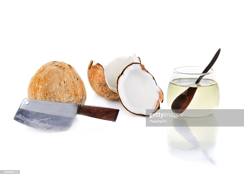 coconut oil with big knife and piece of coconut : Stock Photo