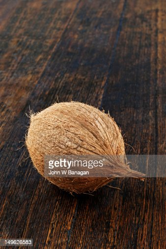 A coconut on an old wooden table : Stock Photo