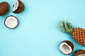 Coconuts and pineapple on blue background with copyspace