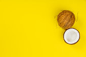 Coconuts on yellow background, flat lay, copy space