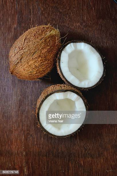 Coconuts-whole and broken on a wooden table