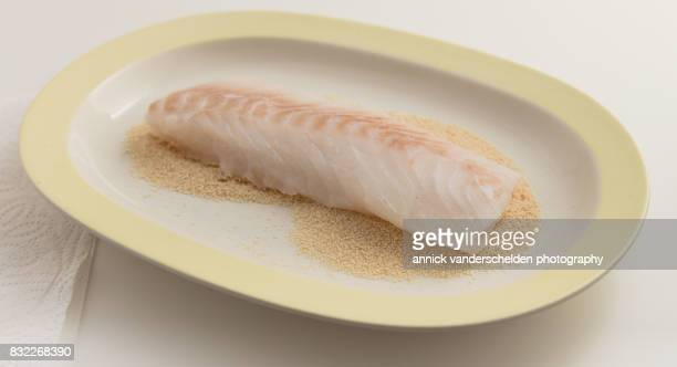 Cod on breadcrumbs in a long breading plate.