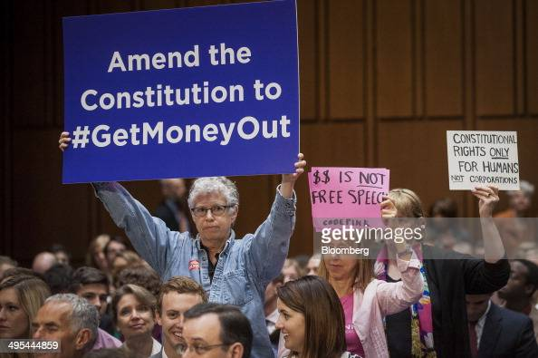 Code Pink activists hold up signs in support of a proposed constitutional amendment on campaign finance during a Senate Judiciary Committee hearing...