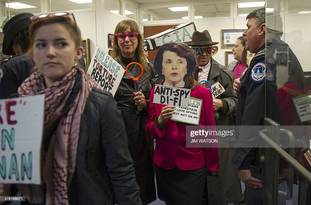 Code Pink Co-founder Medea Benjamin (C-behind Dianne Feinstein mask) and protester Tighe Barry (3rd R) are escorted with other protesters by US Capitol Police from Chairman of the Senate Intelligence Committee Chairman Dianne Feinstein's office after holding a demonstration to 'expose her two-faced stance on spying' in the Hart Senate Office Building on US Capitol in Washington, DC, March 12, 2014. AFP PHOTO / Jim WATSON
