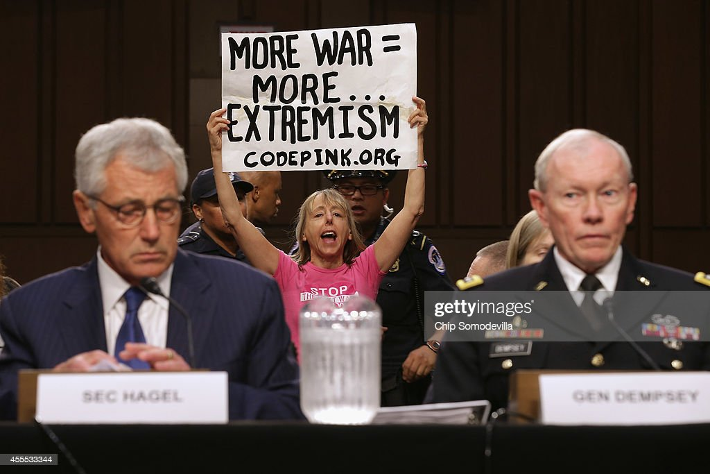 Code Pink for Peace organizer Medea Benjamin (C) protests against U.S. military action in Iraq as Defense Secretary Chuck Hagel (L) and Chairman of the Joint Chiefs of Staff Army Gen. Martin Dempsey testify before the Senate Armed Services Committee in the Hart Senate Office Building on Capitol Hill September 16, 2014 in Washington, DC. Senators questioned the top military and civilian leaders about the threat posed by the terrorist group calling itself the Islamic State of Iraq and the Levant or ISIL.